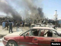 Villagers gather at the site of a truck bomb attack in Orgun on July 15, 2014.