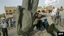 شبان في بغداد يسقطعون تمثال صدام ارضا . ايار 2003
