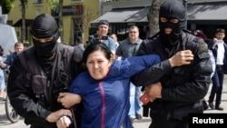 Алматыда полиция арнайы жасағы митингіге шыққан әйелді ұстап әкетіп бара жатыр. 10 мамыр 2018 жыл.