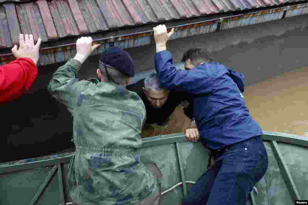 Serbian soldiers help a man out of his flooded house in the town of Obrenovac, Serbia.