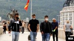 Илустрација - Луѓе со заштитни маски на Камени мост во Скопје