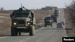 Pro-Russian fighters ride in the back of a truck towing a mobile artillery cannon as they leave the front line and head toward Donetsk on February 23.