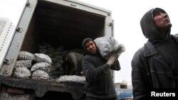 Работники-мигранты разгружают машину с картошкой на одном из московских рынков