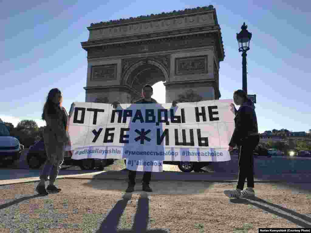 Участники акции в Париже сфотографировались с баннером также у Триумфальной арки.