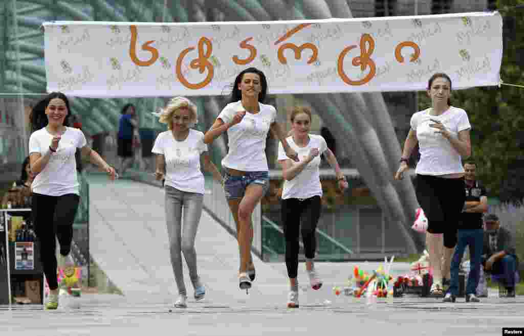 Contestants bear down on the finish line during a high heels race in Tbilisi on June 24. (Reuters/David Midzinarishvili)