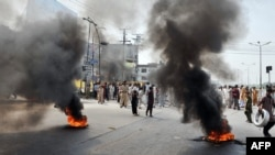 Demonstrators gather behind burning tires as they block a main highway during a protest in Rawalpindi on September 21.