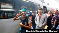 Migrants walk to board a train to Germany at a railway station in Vienna on September 5.