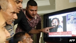 Iraqis watch Arabic satellite news channel Al-Arabiyah as it shows an image that was circulating on the Internet purporting to show the dead body of Al-Qaeda mastermind Osama bin Laden.