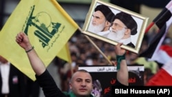 "A Hezbollah supporter chants slogans, as he holds a picture of the late Iran revolutionary founder Ayatollah Khomeini, left, and Iran's Supreme Leader Ayatollah Ali Khamenei, right, during a Hezbollah-organized rally titled ""in solidarity with oppressed Y"