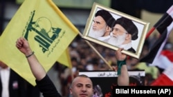 A Hezbollah supporter chants slogans, as he holds a picture of the late Iran revolutionary founder Ayatollah Khomeini, left, and Iran's Supreme Leader Ayatollah Ali Khamenei, right. FILE PHOTO