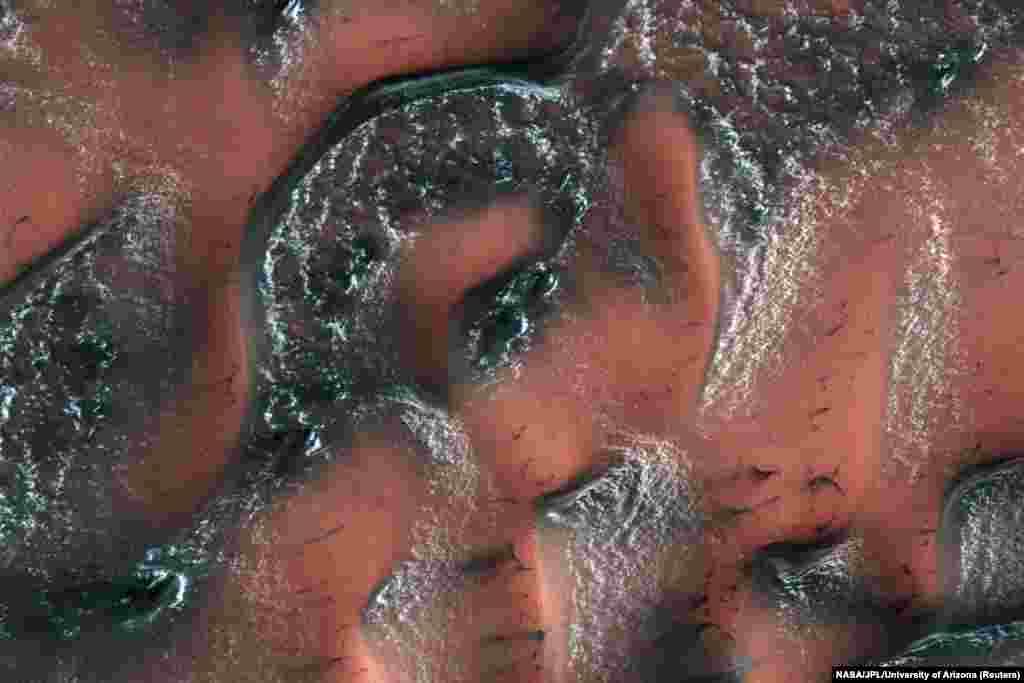 این تصویر که با دوربین آزمایشی تصویربرداری با وضوح بالا (HiRISE) از سطح کره مریخ برداشت شده است، بهار را در بخش شمالی این سیاره نشان میدهد. نقاط سفید این عکس برف هایی هستند که از دی اکسید کربن (یا یخ خشک) ساخته شده اند و تپههای این بخش مریخ را پوشانده اند.