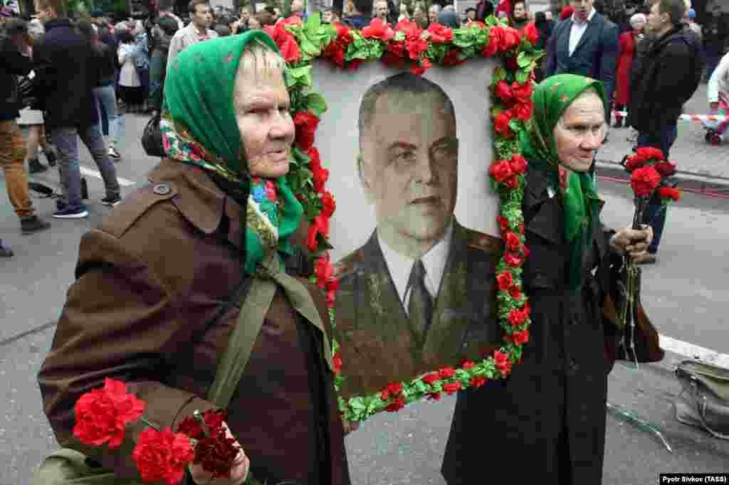 Galina Shkura (left) and Mariya Shkura -- both World War II veterans -- carry a portrait of Chief Marshal Georgiy Zhukov, a symbol of the Soviet Union's victory over Nazi Germany in World War II, as they celebrate Victory Day in Kyiv on May 9. (TASS/Pyotr Sivkov)