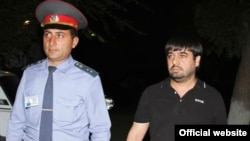 Armenia -- A policeman escorts Sevak Minasian, the arrested son of the deputy prosecutor of Armavir region, 26Sep2012.