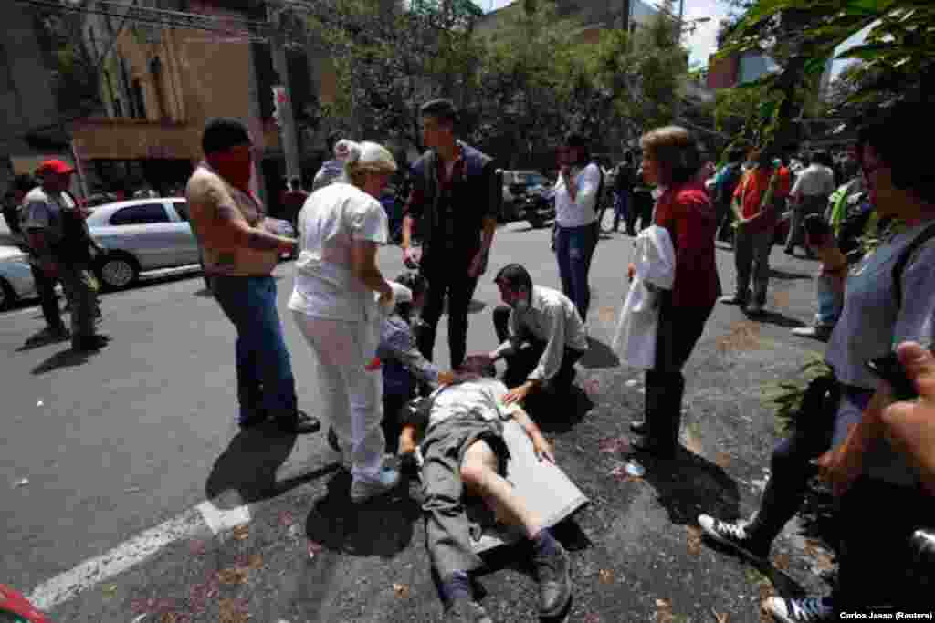 MEXICO -- People help an injured man react after an earthquake hit Mexico City, Mexico September 19, 2017.