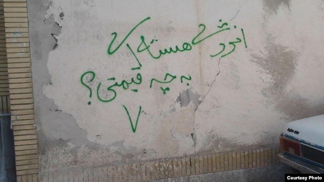 "A graffito in Iran in the green color of the country's opposition movement, which reads ""Nuclear energy, at what price?"""