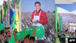 Residents walk past a poster of Turkmen President Gurbanguly Berdymukhammedov during an Independence Day parade in central Ashgabat in October 2008