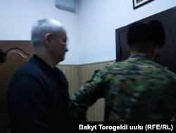 Кубанычбека Кулматова выводят из зала суда.