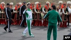 Turkmen President Gurbanguly Berdymukhammedov (center) waves to the media during the starting ceremony of a 500-day nationwide horse race at the historical site of Nisa just outside Ashgabat on May 5, 2016, in preparation for the 2017 Asian Indoor and Martial Arts Games.