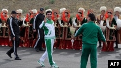 Turkmen President Gurbanguly Berdymukhamedov (center) waves to the media during the starting ceremony in May 2016 for a 500-day nationwide horse race, which was organized as part of Ashgabat's elaborate preparations for the 2017 Asian Indoor and Martial Arts Games.
