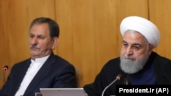 Iranian President Hassan Rouhani and Iranian First Vice President Eshaq Jahangiri (L) attend a cabinet meeting in Tehran, June 19, 2019