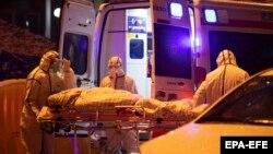 کارمندان صحی چین شخصی را که مصاب به ویروس کرونا شده به شفاخانه انتقال میدهند. 23 January 2020