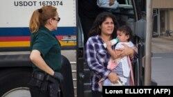 Баласын көтөргөн мигрант аял. 17-июнь, 2018-жыл. Техас.