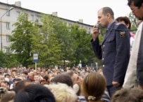 A law-enforcement officer addresses a crowd in the first days of rioting (ITAR-TASS)
