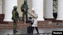 Симферополь әуежайын басып алған айырым белгісі жоқ қарулы әскери адамдар жанынан өтіп бара жатқан әйел. 28 ақпан 2014 жыл.