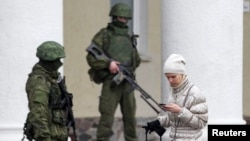 Ukraine -- A woman walks past armed men at the Simferopol airport in the Crimea region, February 28, 2014