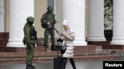 Женщина проходит мимо вооруженных людей в военной форме без опознавательных знаков, блокировавших аэропорт Симферополя. 28 февраля 2014 года.