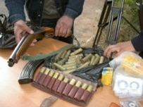 Kyrgyz police show weapons and leaflets allegedly belonging to Hizb ut-Tahrir members seized in March (RFE/RL)