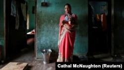 Мать девочки, убитой семьей ее мужа в индийском штате Уттар-Прадеш, с ее фотографией.