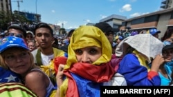 An opposition supporter has a Venezuelan national flag wrapped around her head as she listens to Venezuelan opposition leader Juan Guaido during a gathering in Caracas on February 2, 2019. - Tens of thousands of protesters poured onto the str