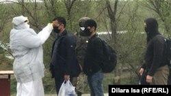 Сотрудник в защитном костюме измеряет температуру тела человека на пропускном пункте на окраине Шымкента. 1 апреля 2020 года.