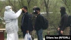 Медработник в защитной одежде проверяет температуру тела на въезде в город. Шымкент, 1 апреля 2020 года.