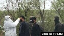Медик в защитном костюме проверяет температуру тела у мужчины на въезде в город. Шымкент, 1 апреля 2020 года.
