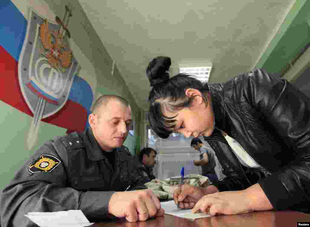 A Central Asian woman fills out forms before her deportation.