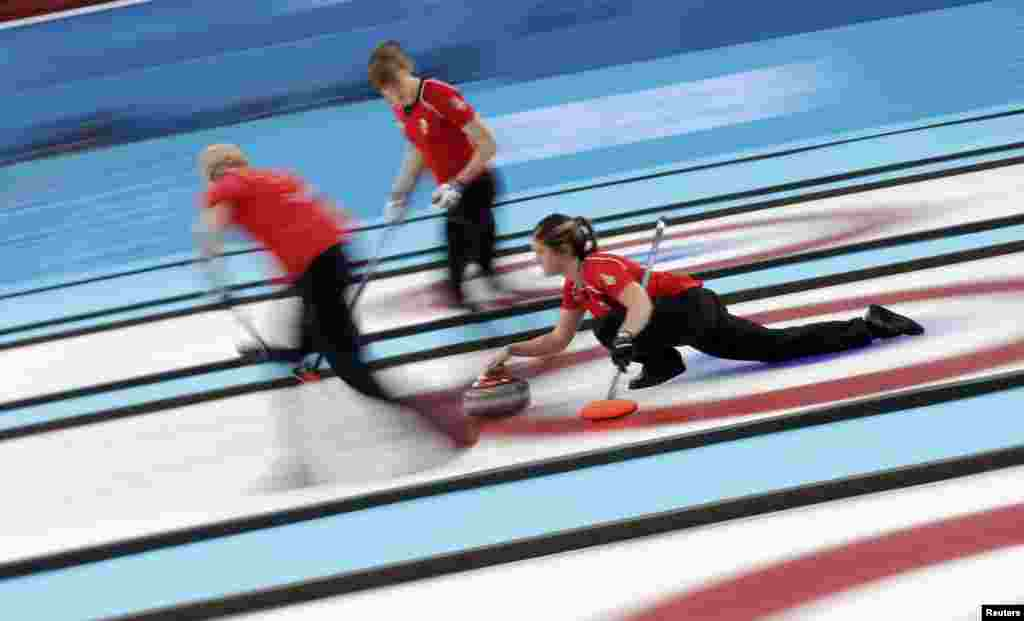 Britain's Vicki Adams (right) delivers a stone as Anna Sloan and lead Claire Hamilton prepare to sweep ahead of it during their women's curling bronze-medal game. (Reuters/Phil Noble)