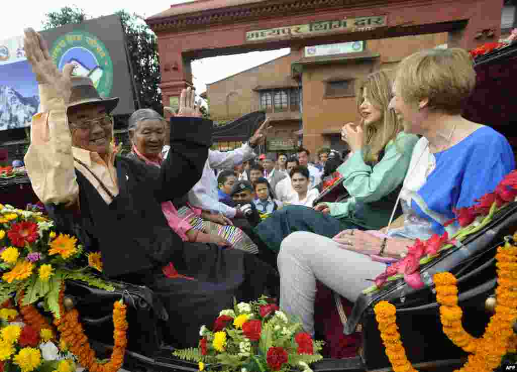 Kancha Sherpa, a member of the 1953 Mount Everest expedition, and Amelia Rose Hillary (second from right), granddaughter of mountaineer Sir Edmund Hillary, wave during a procession for Everest summitteers in Kathmandu.