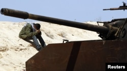 متمرد ليبي يستريح قبالة دبابة معطوبة قرب بنغازي