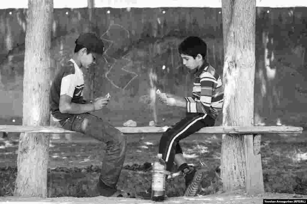 Young boys like Annagurban's nephew Begench (right) still while away the hours in Dostluk by playing cards, something Annagurban himself loved as a child.