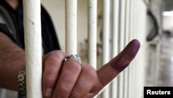 A prison inmate shows his ink-stained finger after voting early inside a prison in Irbil today.