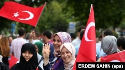 People holding Turkish flags rally on the first anniversary of the failed coup attempt in Istanbul.