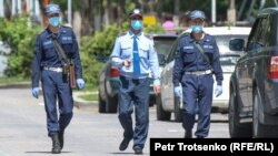 Олмаота шаҳри кўчаларидан бири бўйлаб кетаётган полиция ходимлари, 2020 йил 1 майи (иллюстратив сурат).