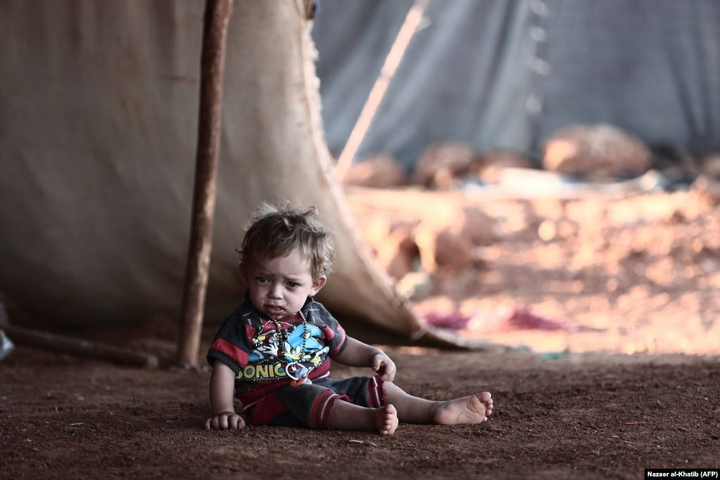 A child sits in front of a tent at a camp for the displaced from the rebel-held Syrian province of Idlib, in the village of Al-Ghadfa, southeast of the province. The Syrian regime and its ally Russia are threatening an offensive to retake the northwestern province, Syria's last rebel bastion. (AFP/Nazeer Al-Khatib)