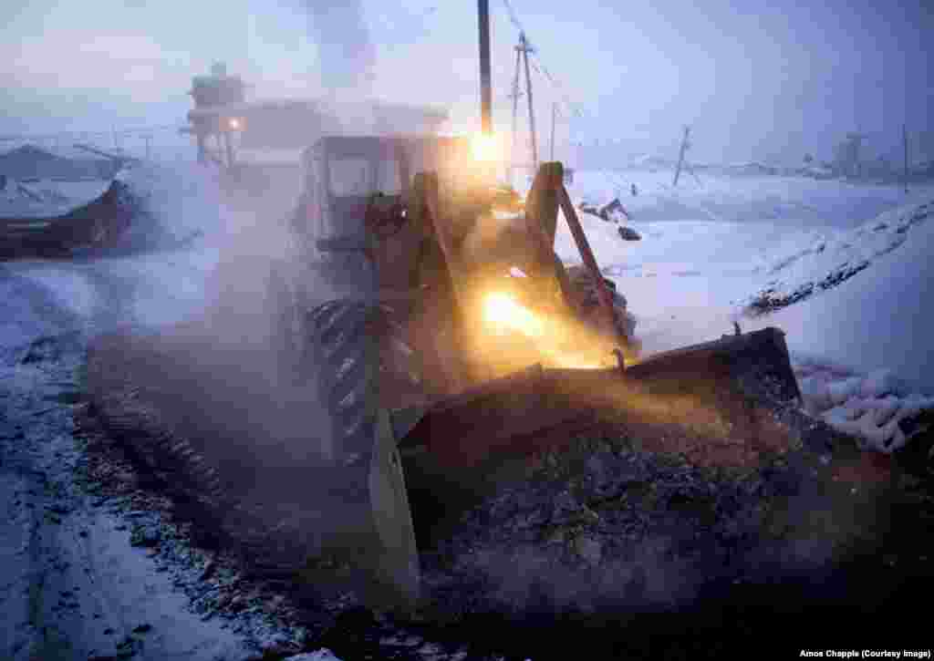A bulldozer dumps coal ash burned by the village's heating plant. The plant works through the day and night to pump hot water through the pipes of the village.
