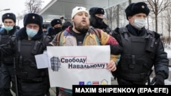 """Police officers detain a protester holding a poster showing Russian President Vladimir Putin that says """"Freedom for Navalny"""" during an unauthorized protest in support of the Russian opposition leader Aleksei Navalny in Moscow earlier this month."""