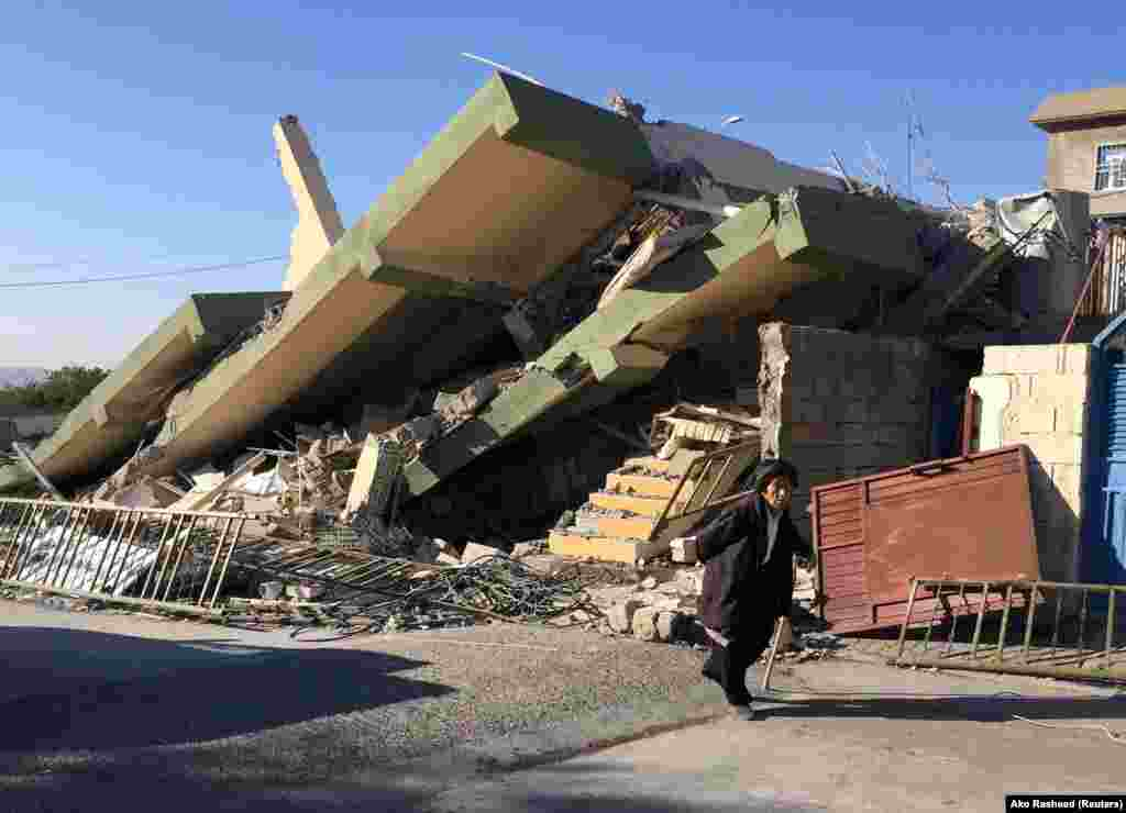 A man walks past a damaged building in Darbandikhan in Sulaimaniya Governorate, Iraq.