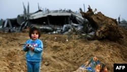 A Palestinian girl stands amid the ruins of destroyed houses on the outskirts of Jabalia refugee camp in the northern Gaza Strip on January 19.
