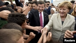 Turkish Prime Minister Ahmet Davutoglu (center) and German Chancellor Angela Merkel are greeted by refugees in Nizip refugee camp on April 23.